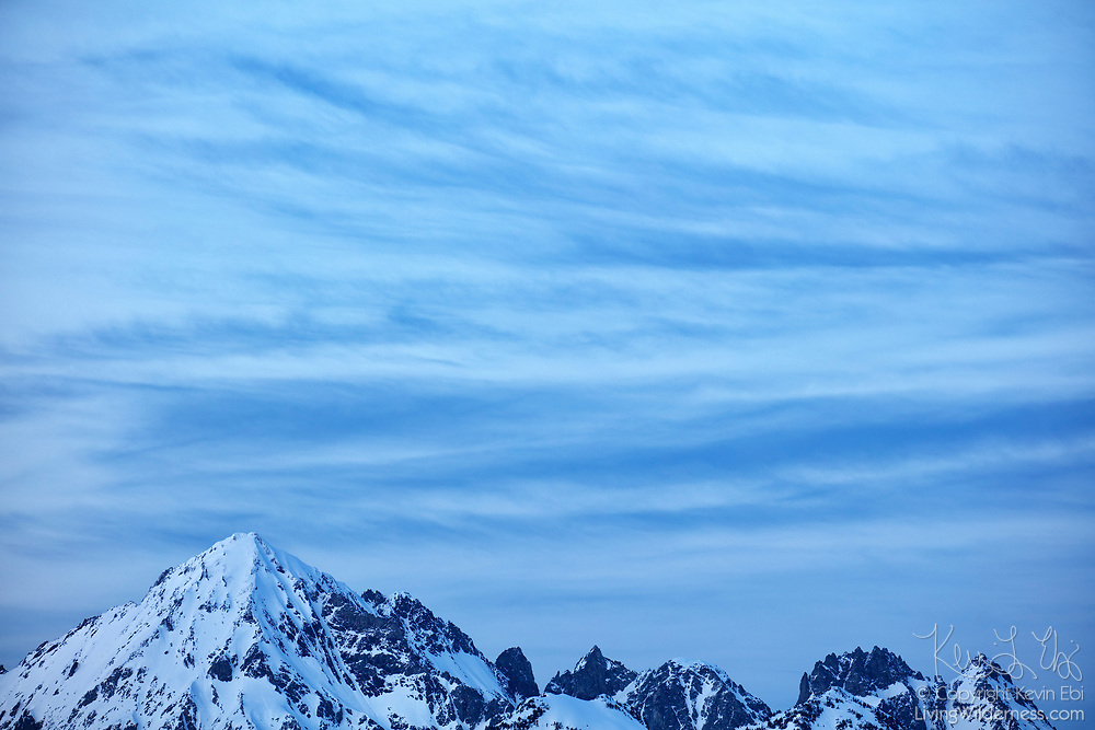 Wispy cirrus clouds fill the sky over Mount Larrabee and the Boulder Peaks in the North Cascades of Washington state. Mount Larrabee, which stands 7,865 feet (2,397 meters) is part of the Skagit Range, which is a sub-range of the North Cascades. It is located less than a mile and a half south of the Canadian border and was originally known as Red Mountain. During the summer months, its red peak, caused by the oxidation of iron in its rock, is distinct.