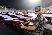 A member of the Kent State University Army ROTC helps control a large American flag during the halftime Heroes' Night commemoration.