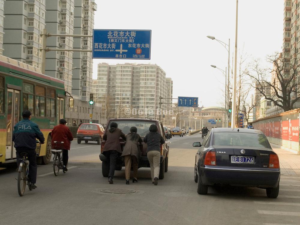 3 women pushing a broken down car Beijing China