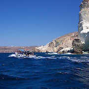 Tourists & Beach lovers alike pack the small shuttle service boats that take people to the three geological spectacular beaches in Akrotiri - Rounding the cliff to White beach in choppy water