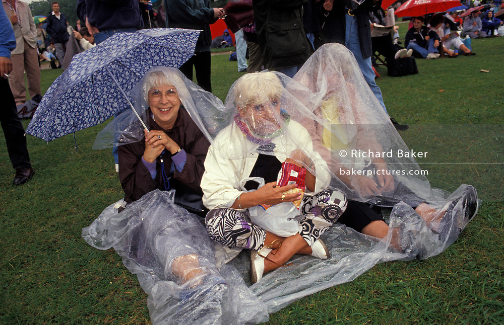 Rain-soaked opera fans sit on wet grass before the perfoamance by Italian operatic tenor Luciano Pavarotti during the free Party in the Park concert to celebrate his 30 years in opera, on 30th July 1991 in London's Hyde Park, on 30th July 1991, in London, England. A crowd of 100,000 stood in the rain to watch Pavarotti perform 20 arias by Verdi, Puccini, Bizet and Wagner. VIPs the Princess of Wales, Prime Minister John Major and Michael Caine were soaked in heavy rain along with everyone else sitting on the grass cowering beneath tarpaulins. Pavarotti helped bring an otherwise high-brow artform to the ordinary Man after the BBC used his rendition of Nessun Dorma to theme their World Cup TV coverage.