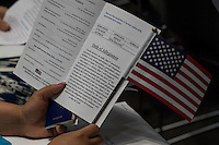 A U.S. citizen applicant holds an American flag and a program during a naturalization ceremony at the Evo A. DeConcini U.S. Courthouse in Tucson, Arizona, U.S., on Friday, Sept. 16, 2016. Photographer: David Paul Morris/Bloomberg