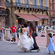 Bride in wedding dress with maid of honor and flower girl walking through the Piazza del Campo, Siena, Italy<br />