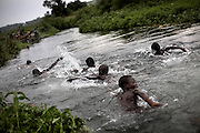 Children from a nearby IDP site swim in a river running through the town of Kichanga, in North Kivu province, DRC, on Saturday, Feb. 16, 2008.