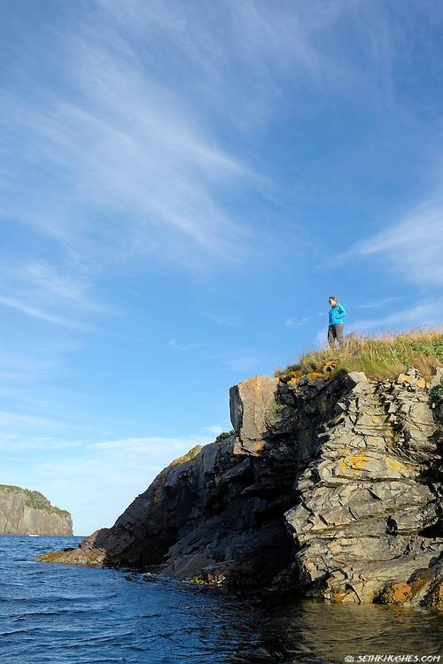 A woman overlooks Trinity Bay in Newfoundland, Canada