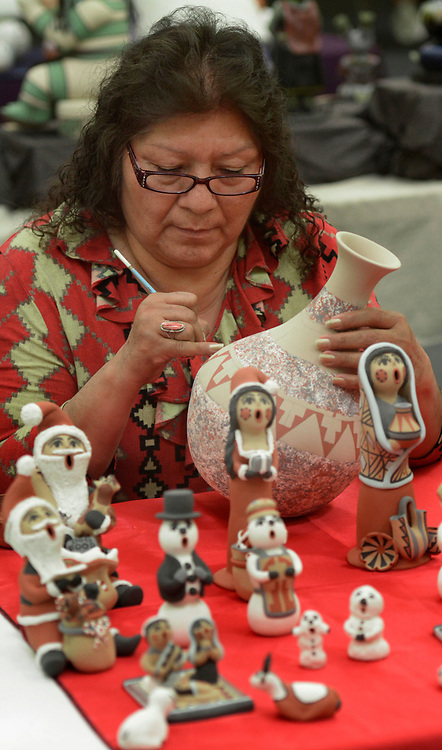gbs031917d/ASEC --Artist Cindy Fragua of Jemez Pueblo applies a slip to her pottery vase while sitting at her table at the Jemez Pueblo Artisan Fair at Congregation Albert on Sunday, March 19, 2017.  This was Congregation Albert Bortherhood's 2nd Annual Jemez Pueblo Artisan Fair in conduction with the Jemez Arts and Crafts Association.