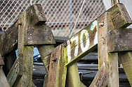 wood trestles wit painted numbers in white paint, and covered in moss showing rusty bolts