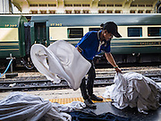 "03 JANUARY 2017 - BANGKOK, THAILAND: A State Railways of Thailand worker sorts linens after a train arrived at Hua Lamphong Train Station in Bangkok Tuesday. Travelers flocked to Bangkok bus and train stations Tuesday, the last day of the long New Year's weekend in Thailand. The New Year holiday in Thailand is called the ""seven deadly days"" because of the number of fatal highway and traffic accidents. As of Monday Jan 2, 367 people died in highway accidents over the New Year holiday in Thailand, a 25.7% increase over the same period in 2016.          PHOTO BY JACK KURTZ"