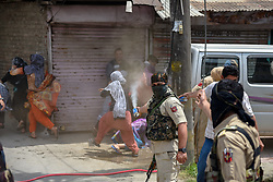 May 13, 2019 - Srinagar, Jammu and Kashmir, India - Kashmiri Protesters are seen running for cover as Indian forces use tear gas smoke canisters to disperse Protesters during the demonstration in Srinagar..Indian forces in Srinagar fired pellets and tear gas smoke canisters to disperse Protesters, who were demonstrating against the alleged rape of three year old girl from north Kashmir Bandipora. (Credit Image: © Idrees Abbas/SOPA Images via ZUMA Wire)