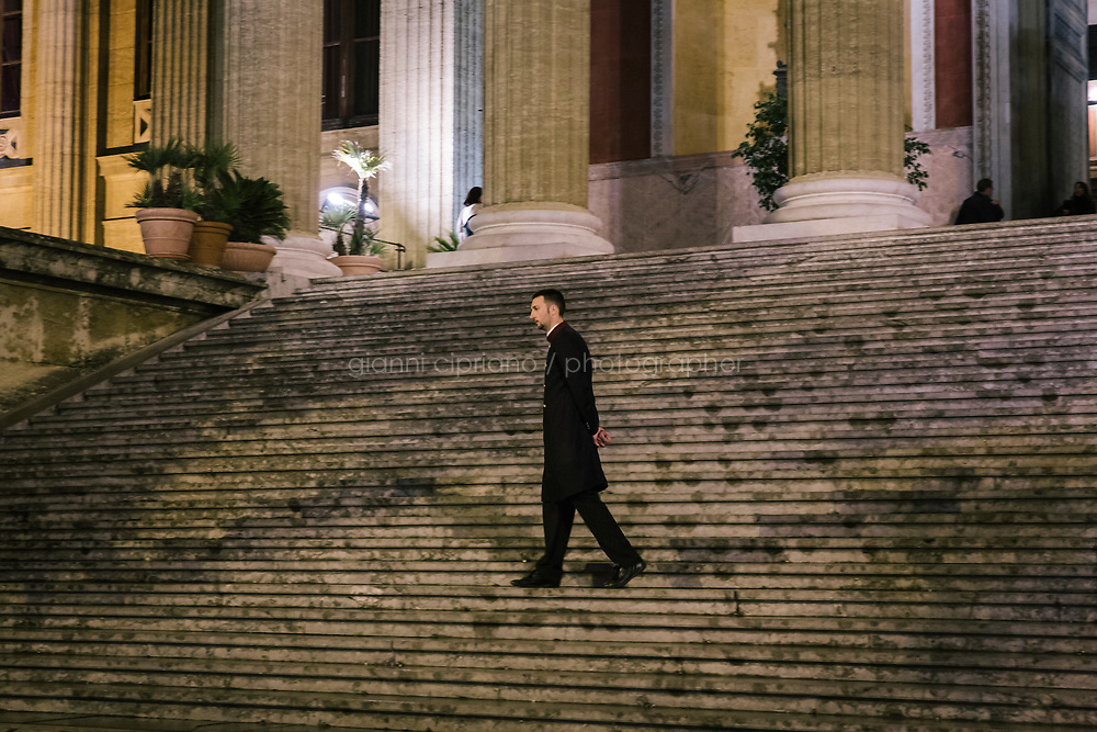 PALERMO, ITALY - 18 FEBRUARY 2018: An usher of the Teatro Massimo is seen here at the main entrance of the theatre during the dress rehearsal of &quot;Don Quixote&quot; at the Teatro Massimo in Palermo, Italy, on February 18th 2018.<br /> <br /> The Teatro Massimo Vittorio Emanuele is an opera house and opera company located  in Palermo, Sicily. It was dedicated to King Victor Emanuel II. It is the biggest in Italy, and one of the largest of Europe (the third after the Op&eacute;ra National de Paris and the K. K. Hof-Opernhaus in Vienna), renowned for its perfect acoustics. It was inaugurated in 1897.