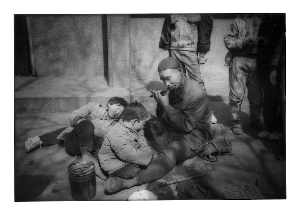 Blind flutist and his blind children on a sidewalk in the wintertime.  Xi'an, Shaanxi Province, China.  1996