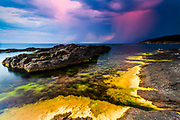 Red rainy clouds at sunset by the sea shore