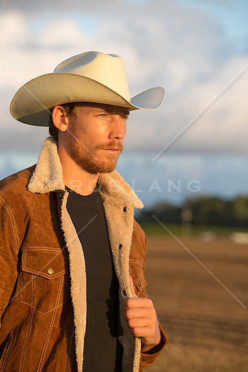 cowboy enjoying a sunset on a ranch