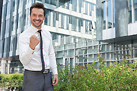 Portrait of successful businessman standing outside office building