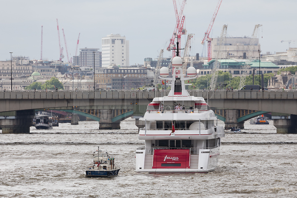 """© Licensed to London News Pictures. 16/06/2018. London, UK.  Bruce Grossman's 180 feet long superyacht, Forever One sails on the River Thames in London after passing under Tower Bridge. Bruce Grossman is one of the richest men in Mexico (estimated net worth of USD1.5 billion) and shareholder of Arca Continental, the second largest Coca-Cola bottler in Latin America and third largest in the world. The unusual red colour scheme of the yacht reflects Grossman's significant Coca-Cola business interests and the yacht also features a reverse bow, fold-down balconies and a beach club with large window in the transom. The name Forever One refers to Bruce's wife Elsa, the childhood best friend of his younger sister and who later became Grossman's """"forever one""""..  Photo credit: Vickie Flores/LNP"""
