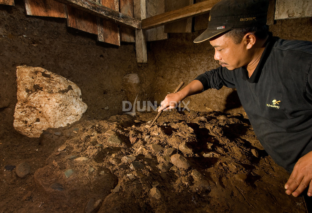 Thomas Sutikna, the leader of the Liang Bua dig from the Indonesian Center for Archaeology, examines a tool manfacturing site left by some of the earliest modern humans to arrive at the cave. Modern human tools post-date those of the Flores hobbit, Homo floresiensis.