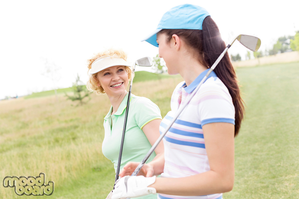Happy female golfers talking at golf course