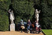 Muslim and European women sit in sunshine at National Trust's Hughenden manor property gardens, once home to Benjamin Disraeli