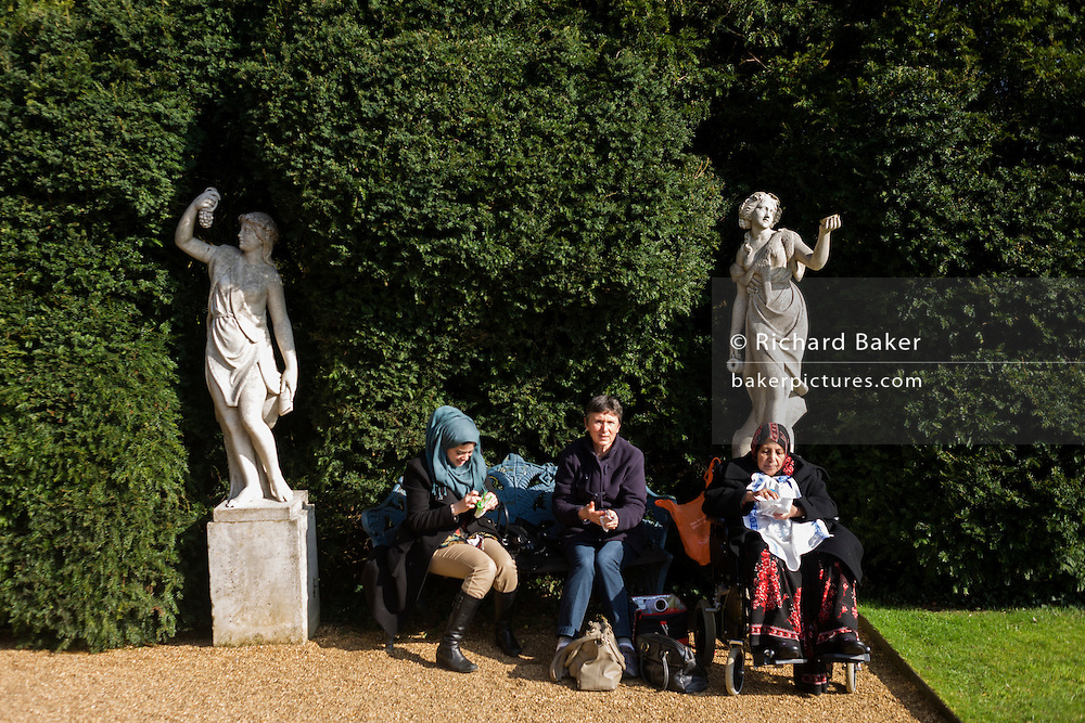 Muslim and European women sit in sunshine at National Trust's Hughenden manor property gardens, once home to Benjamin Disraeli