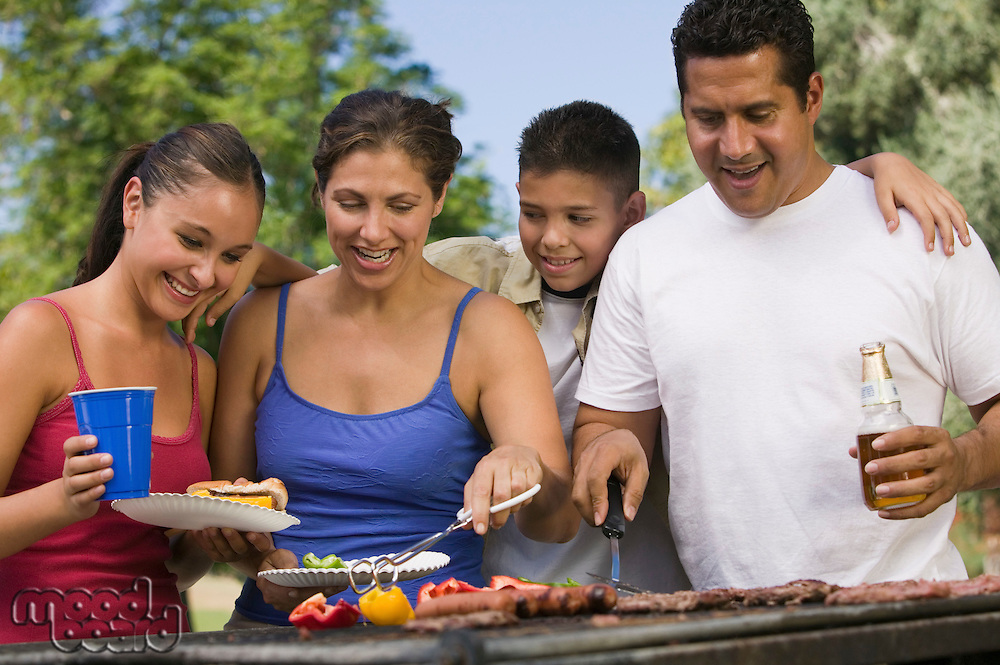 Boy (13-15) with family at outdoor grill.
