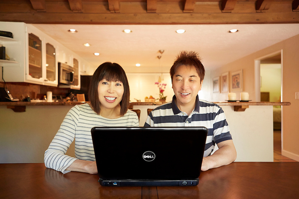 Lifestyle image of laughing Oriental middle age couple while watching YouTube comedy on Dell laptop at dining table inside house