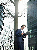 Young man in suit standing under tree outside office building reading newspaper