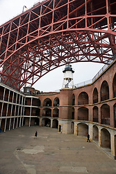 Interior courtyard and light house of Fort Point National Historical Park with arched span of the Golden Gate Bridge in the background, San Francisco, California