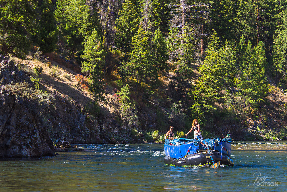 Swamper boat with supplies makes its way down the Middle Fork of the Salmon River with two tough ladies manning the oars.