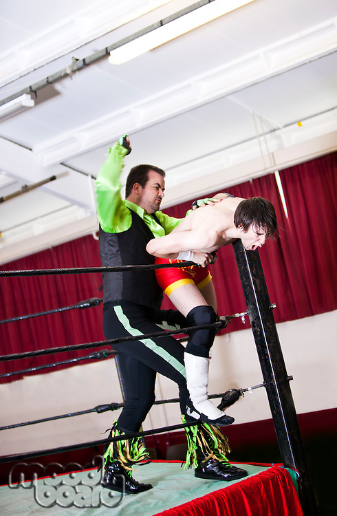 Full-length of young man hitting rival in wrestling ring
