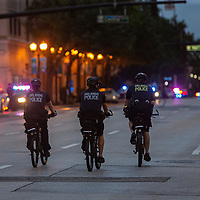 Orlando Bike Police look for curfew violators on Wednesday, June 3, 2020, in Orlando, Fla., as people leave a protest over the death of George Floyd. Floyd died after being restrained by Minneapolis police officers on May 25.  (Alex Menendez via AP)