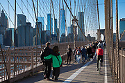 Tourists and local people stroll and cycle across Brooklyn Bridge towards Manhattan, New York City