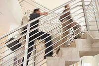 Businessmen climbing stairwell low angle view