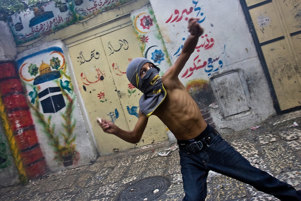 A masked Palestinian hurls stones at Israeli police during clashes in Jerusalem's old city on October 25, 2009. Clashes erupted between Israeli police and Palestinians in and around the Al-Aqsa mosque compound in the latest violence to shake Jerusalem's flashpoint site holy to Muslims and Jews.