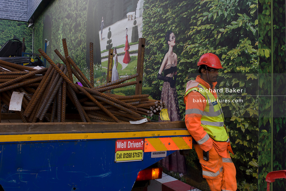 With a background of hanging hoarding media, workmen organise delivery of construction materials on the back of a lorry, to a Dior shop being refurbished in central London.