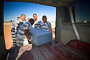 "18 MARCH 2010 - SURPRISE, AZ: Inmates on the ""Chain Gang"" pull a casket out of the funeral home panel van during the interment of indigent county residents in White Tanks Cemetery on Camelback Rd. in an unincorporated part of the county near Surprise. The county spent about $2.5 million to inter indigent people in what is Maricopa County's ""potters field."" About 3,000 people, children and adults, are buried in the dusty field west of Phoenix.      PHOTO BY JACK KURTZ"