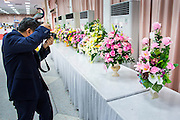 26 NOVEMBER 2012 - BANGKOK, THAILAND:  A man photographs gifts left for the hospitalized King of Thailand at Siriraj Hospital in Bangkok. Siriraj was the first hospital in Thailand and was founded by King Chulalongkorn in 1888. It is named after the king's 18-month old son, Prince Siriraj Kakuttaphan, who had died from dysentery a year before the opening of the hospital. It's reported to one of the best hospitals in Thailand and has been home to Bhumibol Adulyadej, the King of Thailand, since 2009, when he was hospitalized to treat several ailments. Since his hospitalization tens of thousands of people have come to pay respects and offer get well wishes. The King's 85th birthday is on Dec 5 and crowds at the hospital are growing as his birthday approaches. The King is much revered throughout Thailand and is seen as unifying force in the politically fractured country.       PHOTO BY JACK KURTZ