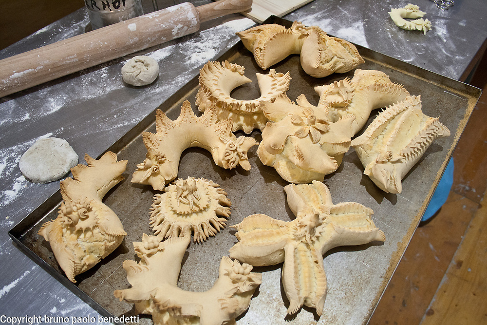 decorated and carved bread shapes after cooking on coounter, Sardinian bread sculpture, the Pani Pintau