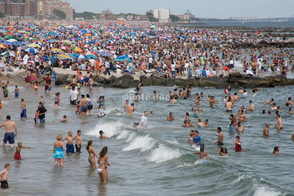 view of the beach at Coney Island on a crowded sunny summer day NY
