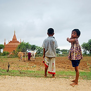 Children waiting by the road while mother works on nearbby field