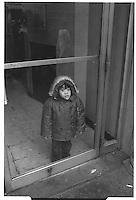 Child behind glass door, New York City. Street photography. 1980