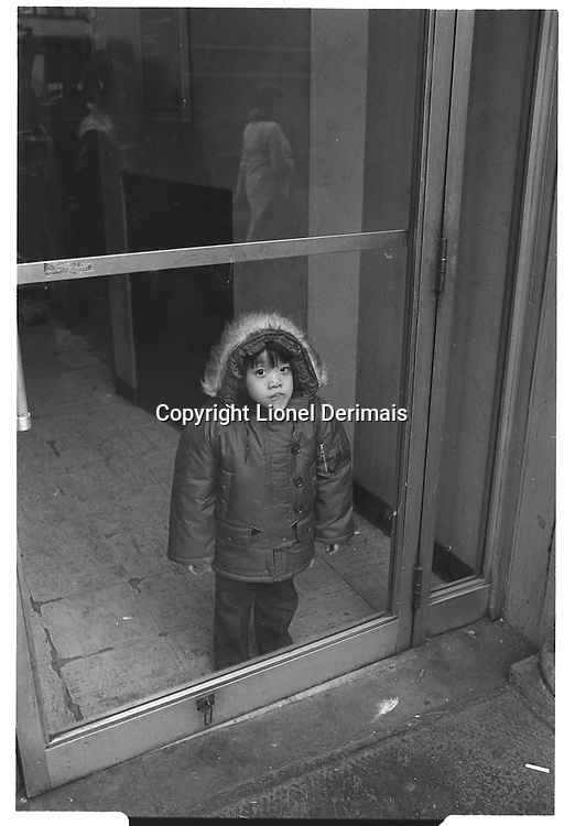 Child behind glass door, New York City. Street photography. 1980