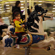 Children ride on the carousel at Lotte World. Lotte World is the world's largest indoor theme park which includes shopping malls, a luxury hotel, and an Ice rink. Opened on July 12, 1989, Lotte World receives over 8 million visitors each year. Seoul, South Korea. 21st March 2012. Photo Tim Clayton