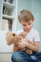 Sad young boy with his teddy bear