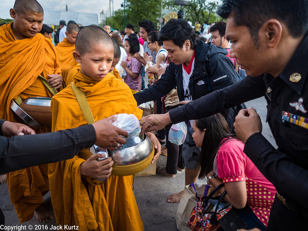 01 JANUARY 2016 - BANGKOK, THAILAND:          People make merit by presenting a Buddhist novice (young monk) with alms during the annual New Year's mass merit making ceremony on at Sanam Luang in Bangkok. The ceremony is sponsored by the Bangkok city government. More than 500 Buddhist monks participated in the ceremony this year. Thais usually go to temples and religious observances to meditate and make merit on New Year's Day.    PHOTO BY JACK KURTZ