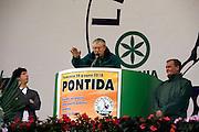 """Umberto Bossi Senator of Lega Nord (North League) at Italian Parliament, speaks at annual gathering in Pontida, June 20, 2010. (L) Renzo Bossi, Regional Concillor and son of Umberto, called """"trota"""" (trout); (R) Roberto Calderoli, Minister for Normativeness Simplification, of Berlusconi Cabinet...Umberto Bossi, senatore della Lega Nord, parla all'annuale raduno della Lega Nord a Pontida, 20 giugno, 2010. (S) Renzo Bossi, consigliere regionale e figlio di Umberto, sopranominato """"trota""""; (D) Roberto Calderoli, Ministro per la semplificazione normativa del governo Berlusconi."""
