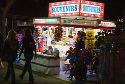 People walking past a lighted souvenir stand at night, California Mid-State Fair, Paso Robles, California, United States of America