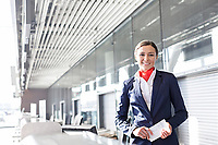 Portrait of young attractive passenger service agent holding boarding pass in airport check in area
