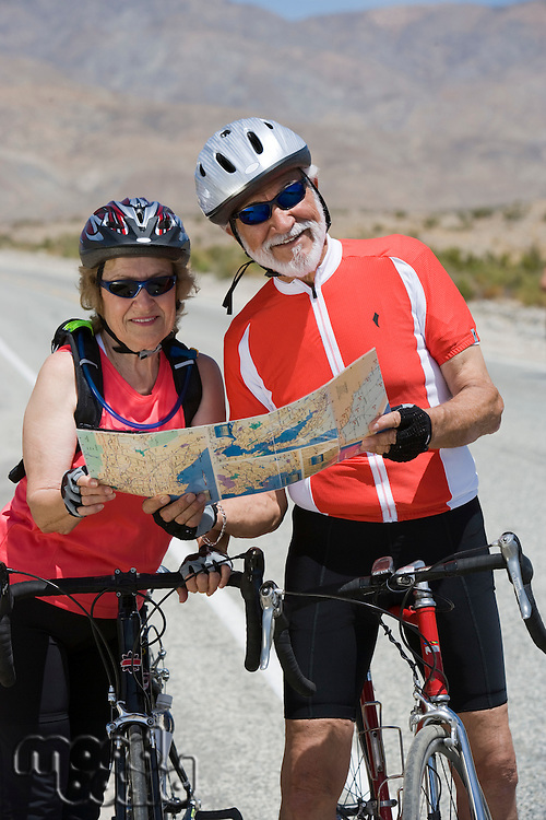 Senior couple with bikes reading map