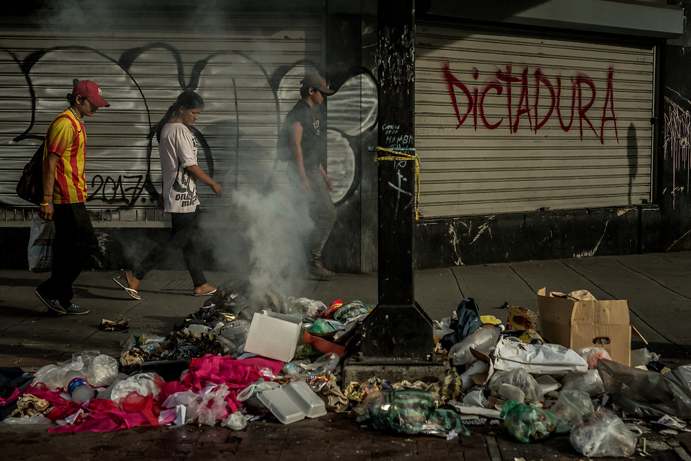"CARACAS, VENEZUELA - JULY 27, 2017: People walk  past a shop closed in support of a national strike, with graffiti on the security door that says, in Spanish: ""Dictatorship"". The political opposition called for a 48 hour national strike for July 26th and 27th, and for their supporters to close businesses, not go to work, and instead create barricades to block off their streets.  Opposition controlled areas of the country were completely shut down.  The strike was called as part of the opposition's civil resistance movement - that began on April 1st, to protest against the Socialist government's attempt to elect a new constituent assembly that will have the power to re-write the constitution, and will threaten democracy.  PHOTO: Meridith Kohut for The New York Times"