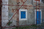 Scaffolding over blue door and window on house restoration project near Castelo Sao Jorge, in Lisbon, Portugal.